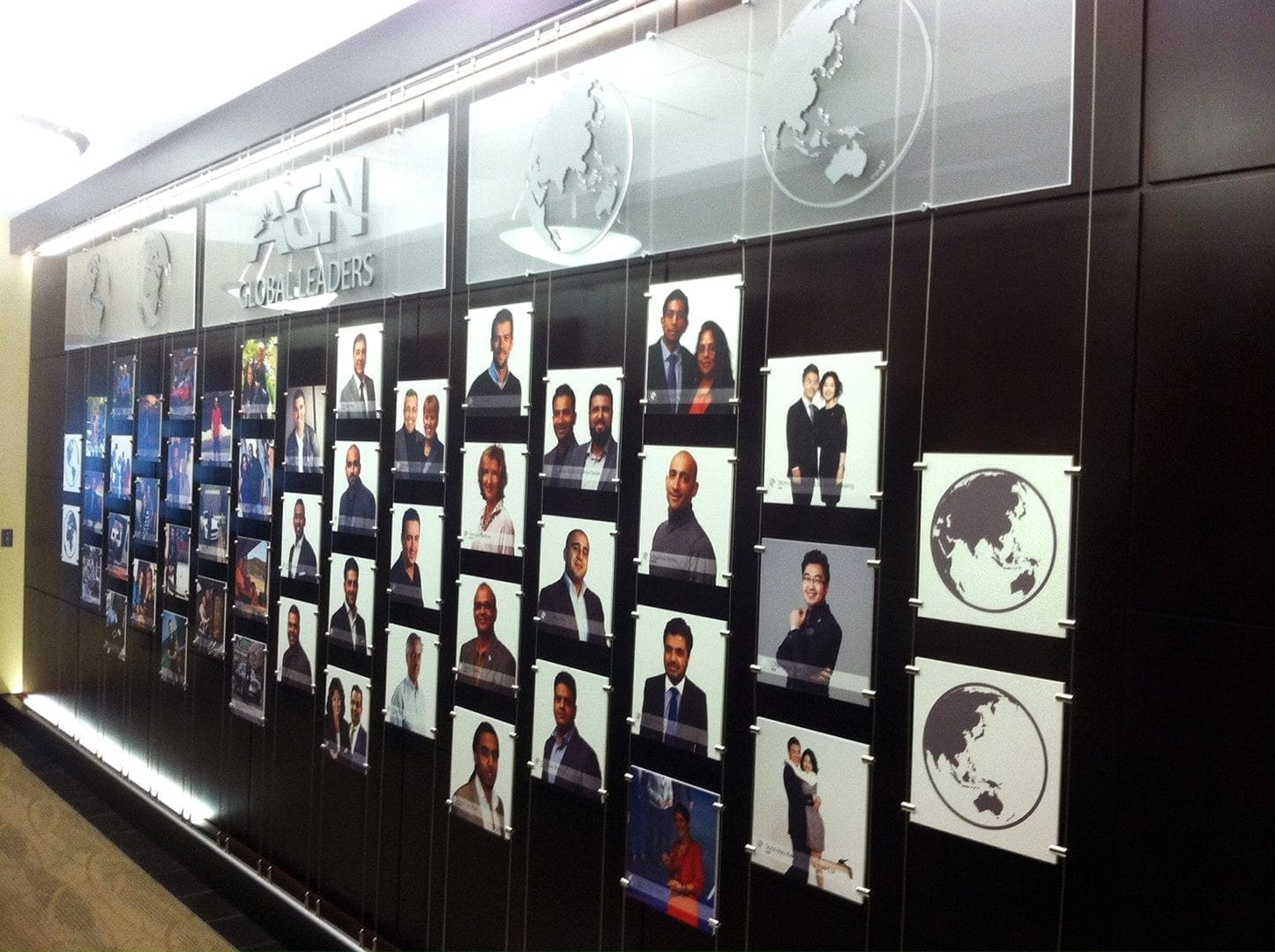 Lobby wall of prints of leaders cable-hung with custom world map graphics and brand logo