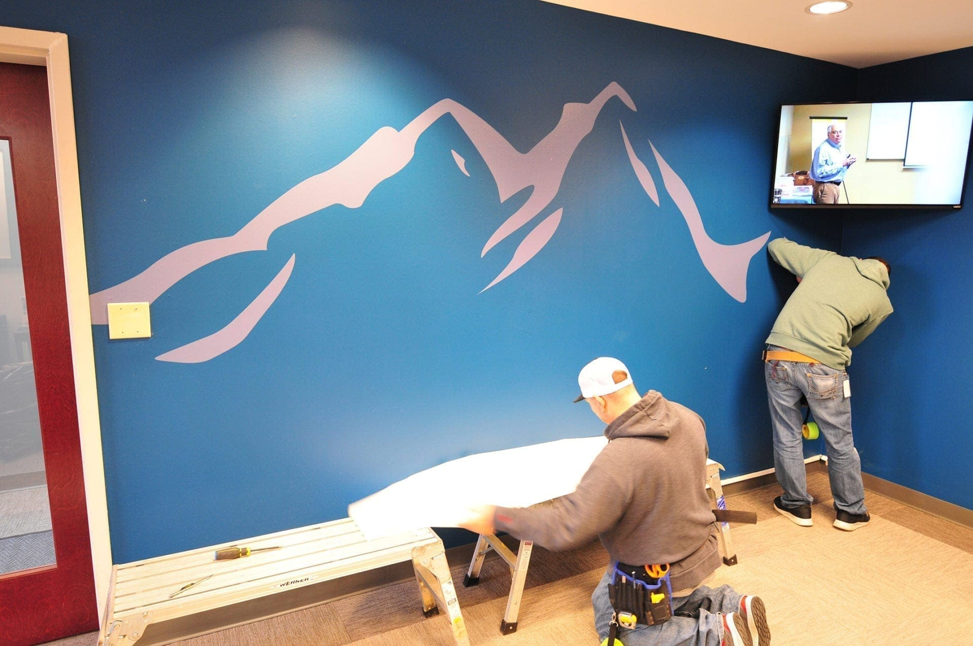 Two workers install custom vinyl logo graphic onto wall at High Point Clinical Trials Center lobby