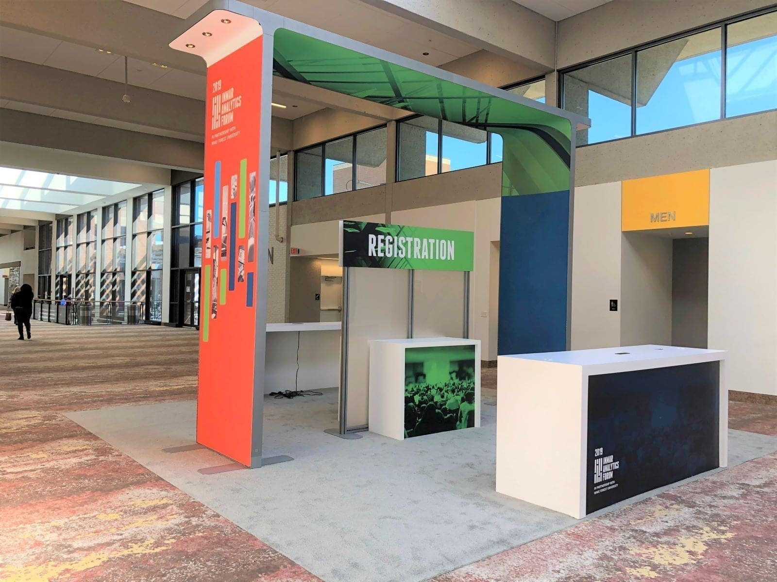 Custom designed and installed Inmar Analytics Forum event registration exhibit with archway, color graphics, and LED lighting