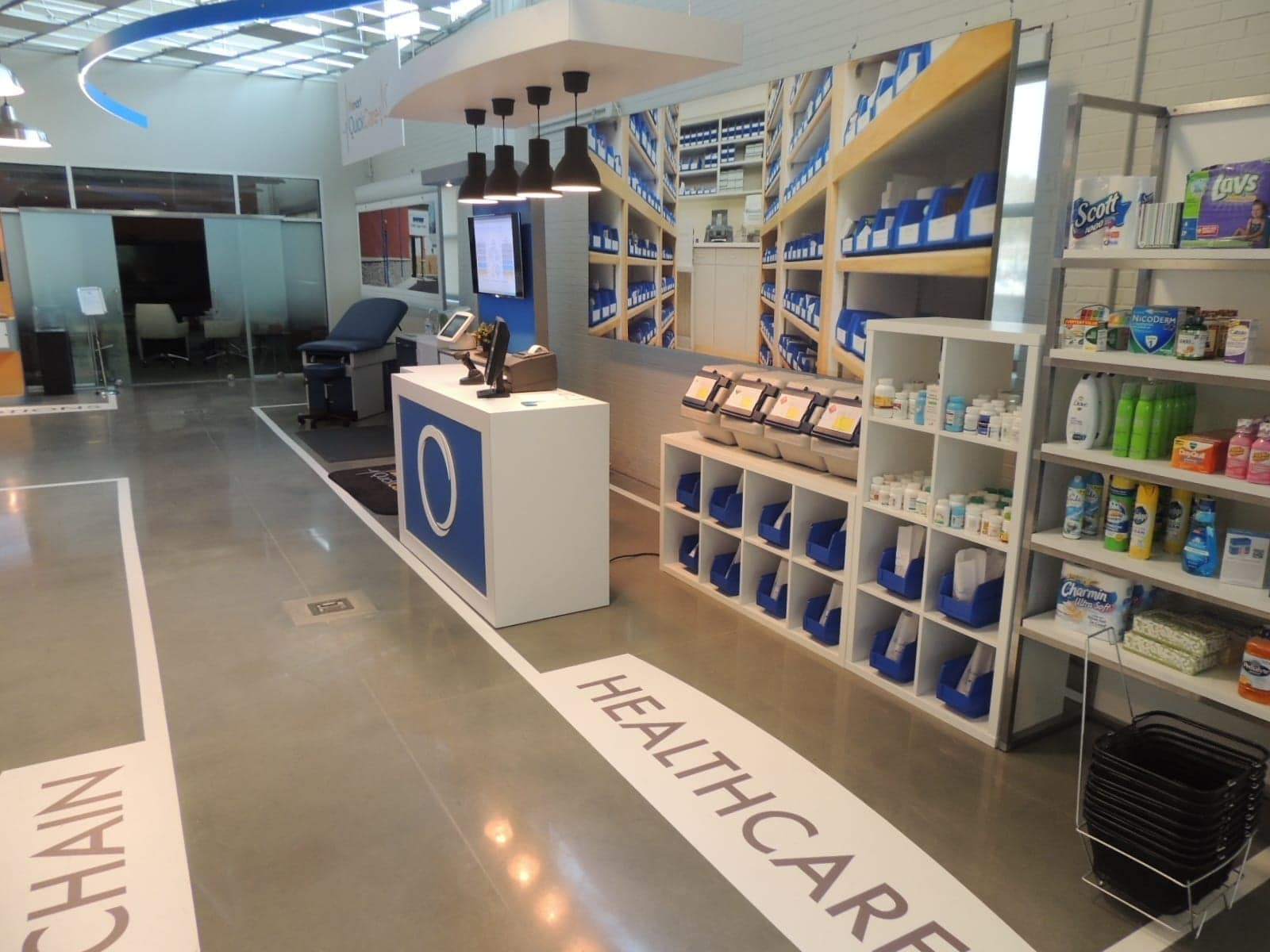 Custom healthcare exhibit with customer engagement kiosk, product shelving and displays, and large vinyl graphic backdrop